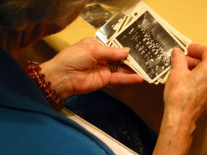 A reunion visitor looks through a handful of old photographs of the Auseklis camp high school.