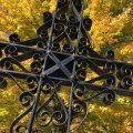 Against a background of a colorful maple tree in autumn, the wrought iron cross marking the grave of Krišjānis Jānis Cielava stands out in Lincoln County's Latvian cemetery